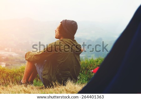 Young hike hipster man sitting at his campsite on the top of hill while enjoying the nature in rainy sunny weather,young man relaxing on the grass enjoying outdoors view and resting after hike, flare - stock photo