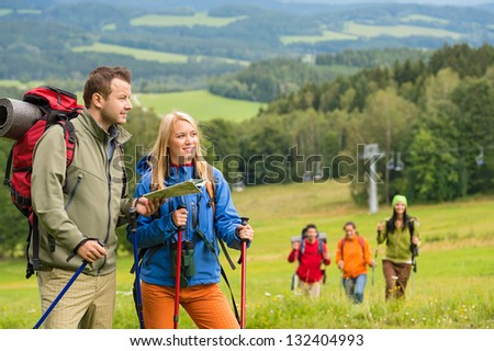 Young hiker friends reading map in natural landscape - stock photo