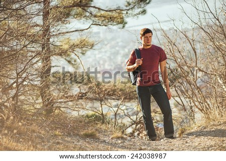 Young hiker man with backpack walking in forest. Hiking and recreation theme - stock photo