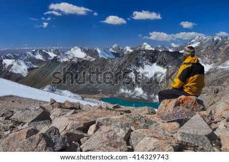Young hiker on mountain summit in scenic Tian Shan range in Kyrgyzstan, Ala Archa national park - stock photo