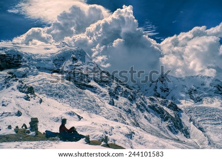 Young hiker sitting in south american Andes in Peru, Ausangate with dramatic clouds forming above the mountains - stock photo