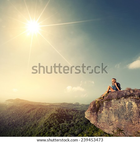Young hiker sitting on top of the mountain at sunny day - stock photo