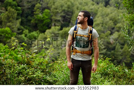 Young hiker with backpack look around while planning mountain walk trip, man hiker get lost in beautiful green forest and looking to laterally copy space area for your text message or information - stock photo