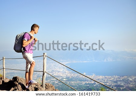 young hiker with backpack standing on top of Vesuvius mountain looking for the panorama of the Naples Gulf - stock photo