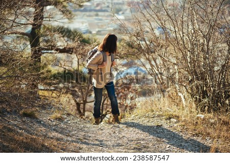 Young hiker woman with backpack looking back in autumn outdoor in highlands. Hiking and recreation theme - stock photo