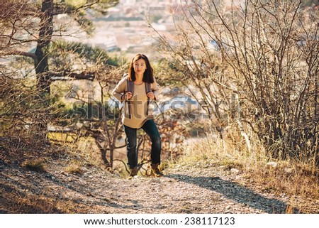 Young hiker woman with backpack trekking in autumn outdoor in highlands. Hiking and recreation theme - stock photo