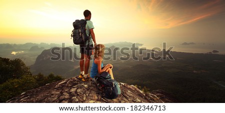 Young hikers enjoying sunrise on top of the mountain after trekking - stock photo
