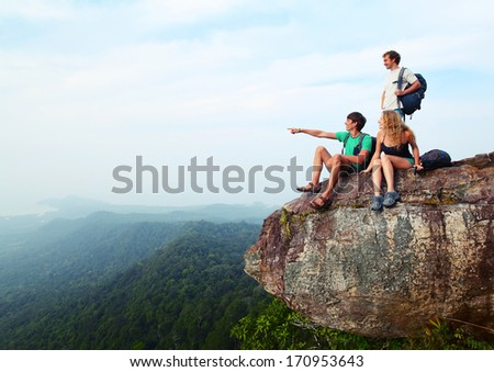 Young hikers relaxing on top of a mountain - stock photo