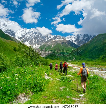 Young hikers trekking in Svaneti, Georgia. Shkhara mountain in the background - stock photo