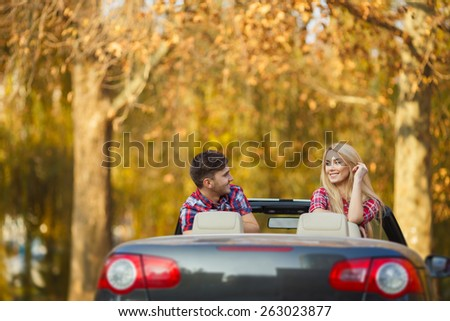 Young hip couple - man and woman - with cabriolet convertible car in summer on a day trip. Couple driving convertible car enjoying a summer day - stock photo