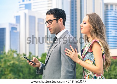 Young hipster couple in moment of mutual disinterest - Concept of breaking up connected to the alienation from new trends and technologies - Ignored girlfriend trying to keep attention from boyfriend - stock photo