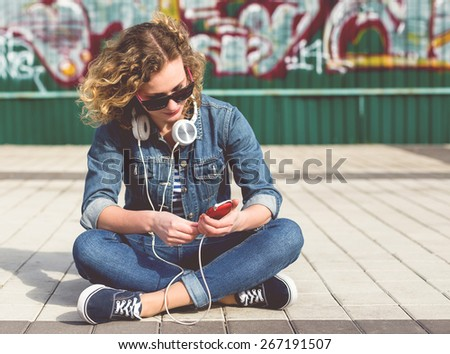 Young Hipster curly woman in the city - stock photo