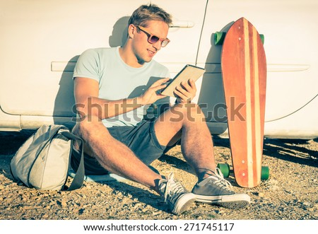 Young hipster fashion guy with computer tablet sitting next his car during road trip - Concept of new trends and technology mixed with vintage lifestyle - Traveler man on retro nostalgic filtered look - stock photo