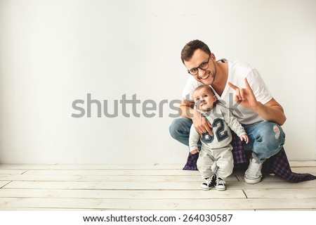 Young hipster father and cute baby boy sitting on rustic wooden floor over white background - stock photo