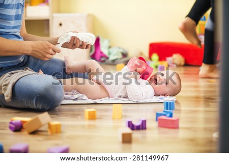 Young hipster father changing nappy to his little baby daughter - stock photo