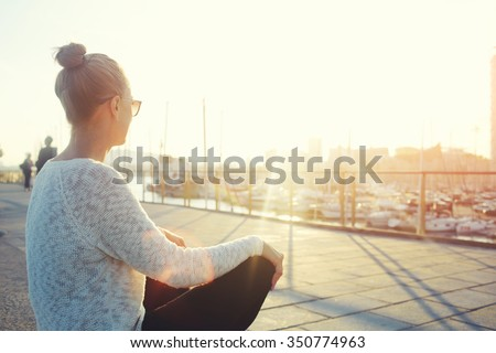 Young hipster girl enjoying sun and good warm day during her recreation time, woman relaxing outdoors after walking in the fresh air, female looking at the landscape while sitting near sea port  - stock photo