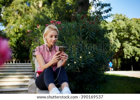 Young hipster girl is chatting via mobile phone in network with her friends and listening to music in headphones, pretty female is reading text message on her cell telephone while relaxing in the park - stock photo
