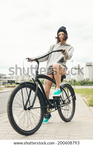 Young hipster girl riding on black bike. Outdoor lifestyle portrait - stock photo