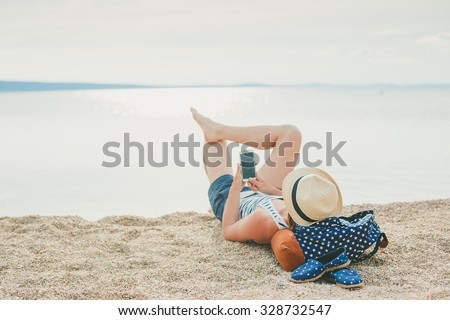 Young hipster girl texting in a smartphone on the beach with the sea in the background  - stock photo
