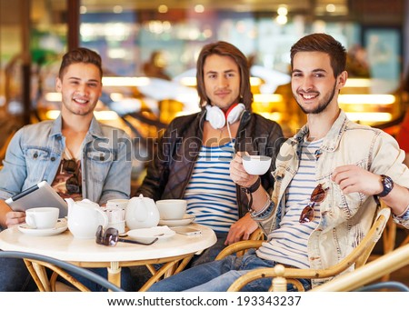 young hipster guys sitting in a cafe chatting and drinking coffee smiling and using tablet computer in cafe - stock photo