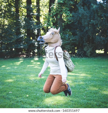 young hipster horse mask woman in the woodland autumn - stock photo