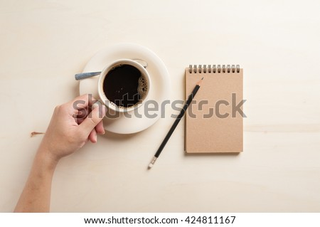 Young hipster male left hand holding coffee cup on wood table beside small notebook with blank area on brown cover in morning time - stock photo