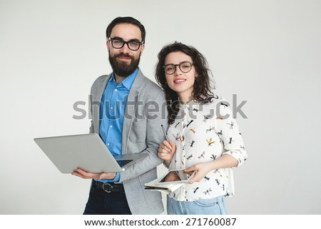 Young hipster man and woman in glasses with laptop and tablet isolated on the blank white background - stock photo