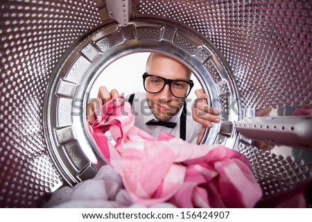 Young hipster man doing laundry View from the inside of washing machine.  - stock photo