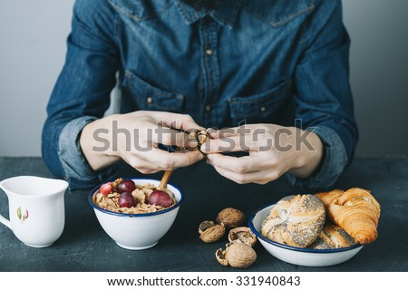 young hipster man having a breakfast on dark table - stock photo