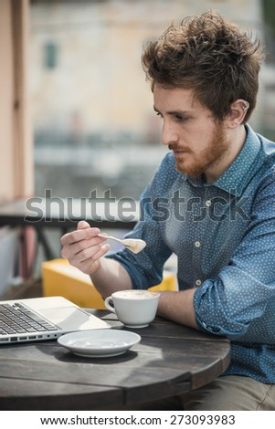 Young hipster man having a coffee at the bar and using a laptop - stock photo