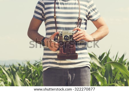Young hipster man holding retro photo camera. - stock photo