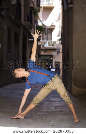 Young hipster man in a urban background practicing yoga - stock photo