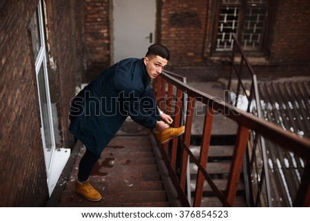 Young hipster man on stairs tying shoelaces on boots. A man wearing in a blue jacket , a white shirt, blue jeans and yellow boots - stock photo