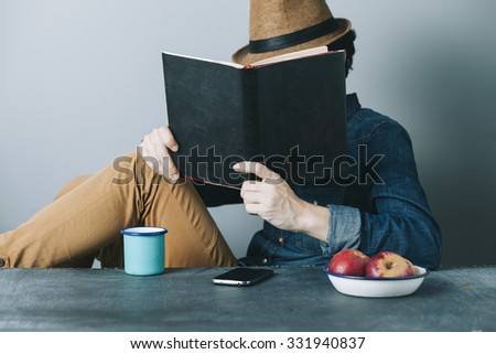 young hipster man reading a book and relaxing - stock photo