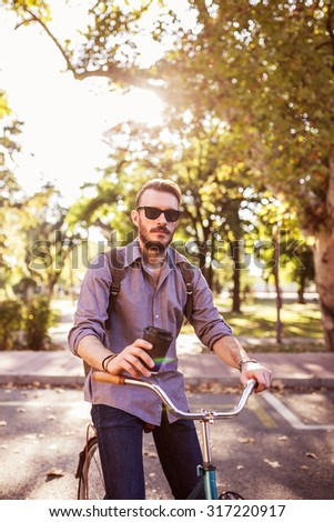 Young hipster man riding vintage bike on city street and drinking to go coffee - stock photo
