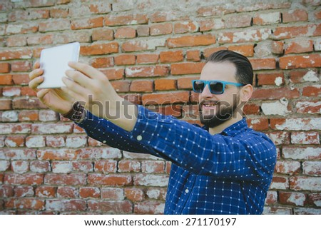 Young hipster man taking a selfie in front of a brick wall. - stock photo