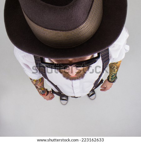 young hipster man wearing  hat and bow-tie and a funny tattoo - stock photo