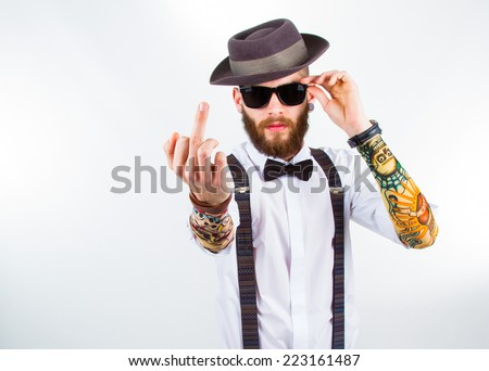 young hipster man wearing  hat , suspenders,   a bow-tie and   a funny tattoo-sleeve showing his f-finger - stock photo