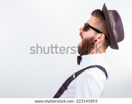 young hipster man wearing  hat , suspenders and bow-tie with open mouth - stock photo