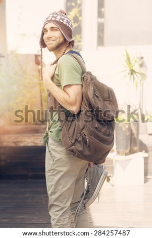 Young hipster man with knit hat and backpack - stock photo