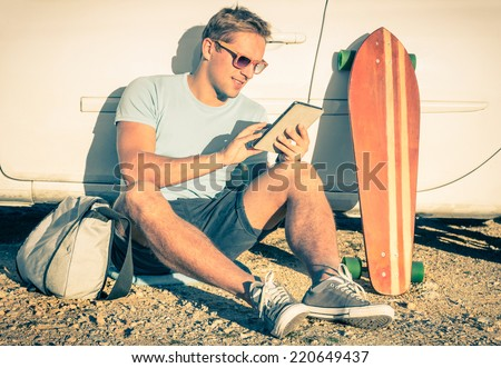 Young hipster man with tablet sitting next his car - Concept of modern technologies mixed with a vintage lifestyle - Retro filtered look - stock photo