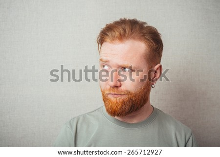 Young hipster red bearded Man Looking Impared - stock photo