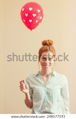 Young hipster redhead woman holding a red balloon with polka dot hearts - stock photo