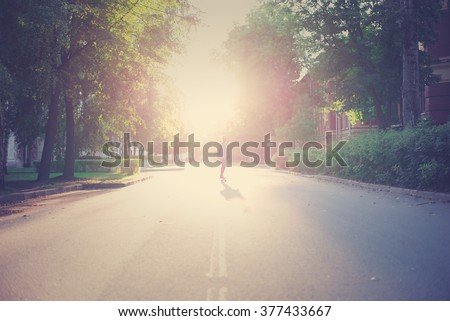Young hipster riding a longboard on the road in the park under the rays of the sunset. - stock photo