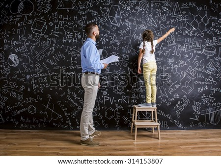 Young hipster school teacher with his pupil in front of big blackboard  - stock photo