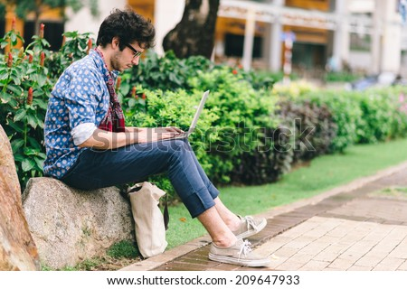 Young hipster sitting on the stone and working on laptop, side view - stock photo