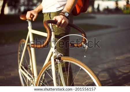 Young hipster style man posing with bicycle on the street sport style picture handsome guy with red backpack ready for trip   - stock photo