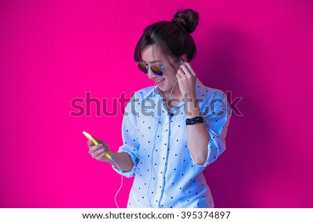young hipster stylish beautiful girl listening to music, mobile phone, headphones, enjoying, denim outfit, smiling, happy, cool accessories, vintage style, having fun  Colorful Background - stock photo
