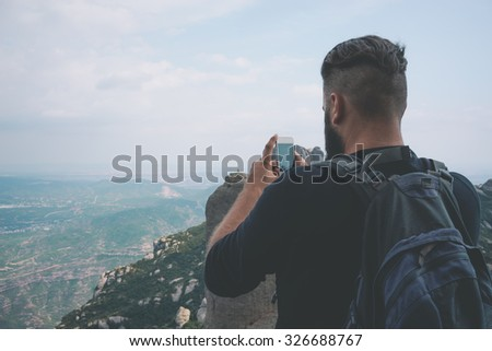Young hipster taking picture with phone camera of landscape - stock photo