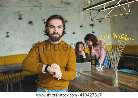 Young hipster with smart watch over two females in cafe - stock photo